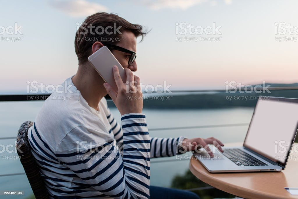 IT Manager working in outdoors cafe, magnificent view of the sea, lake, river in the background stock photo