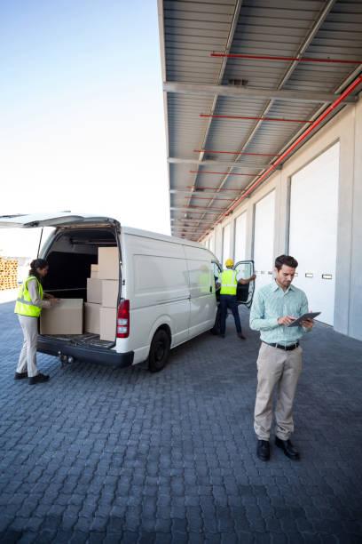 manager für tablet und lager arbeiter laden die kartons - möbel 24 online stock-fotos und bilder