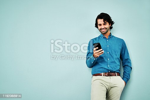Studio shot of a young businessman using a smartphone against a blue background