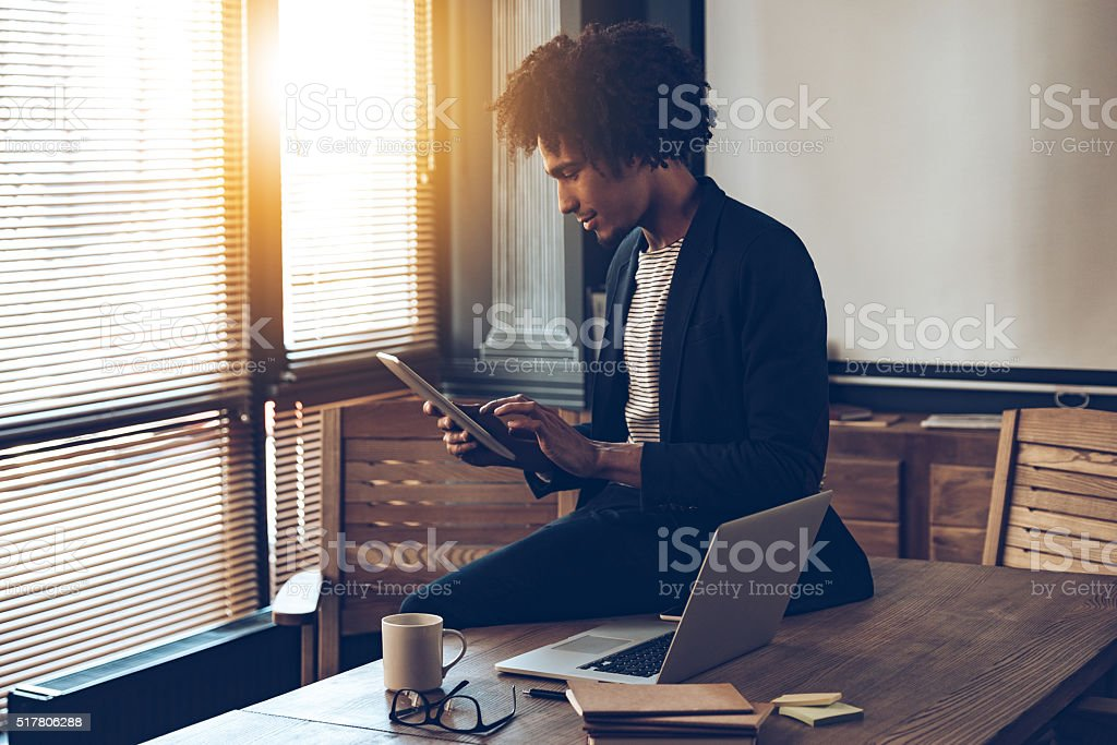 Managing his timetable. Side view of young handsome African man using his digital tablet while sitting on table at his working place Adult Stock Photo