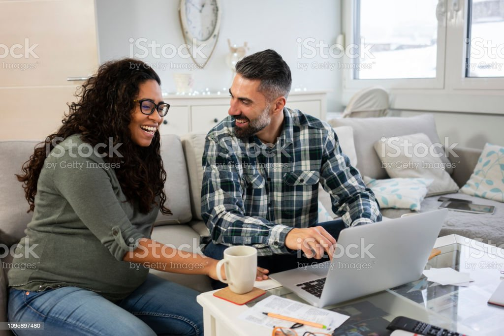 Mature couple working on laptop with bills and paperwork