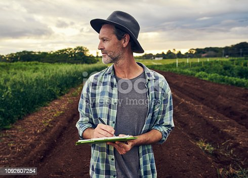 Shot of a mature farmer checking the crops on his farm