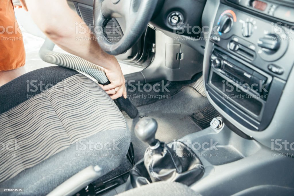 Manc cleaning car with vacuum cleaner stock photo