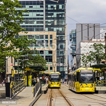 View along the streets in the center of Manchester.  Trams can be seen passing one anouther and people can be seen walking on the pavements.