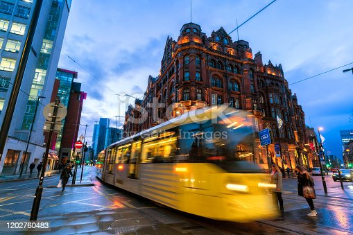 Manchester City centre, City tram approaching with pedestrians walking on the road.
