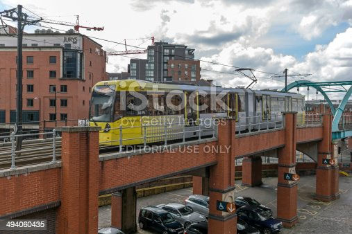 manchester, UK - May 14, 2014: View of a tram in Manchester on a high level bridge in the centre of Manchester.  People including the driver can be seen on the tram.