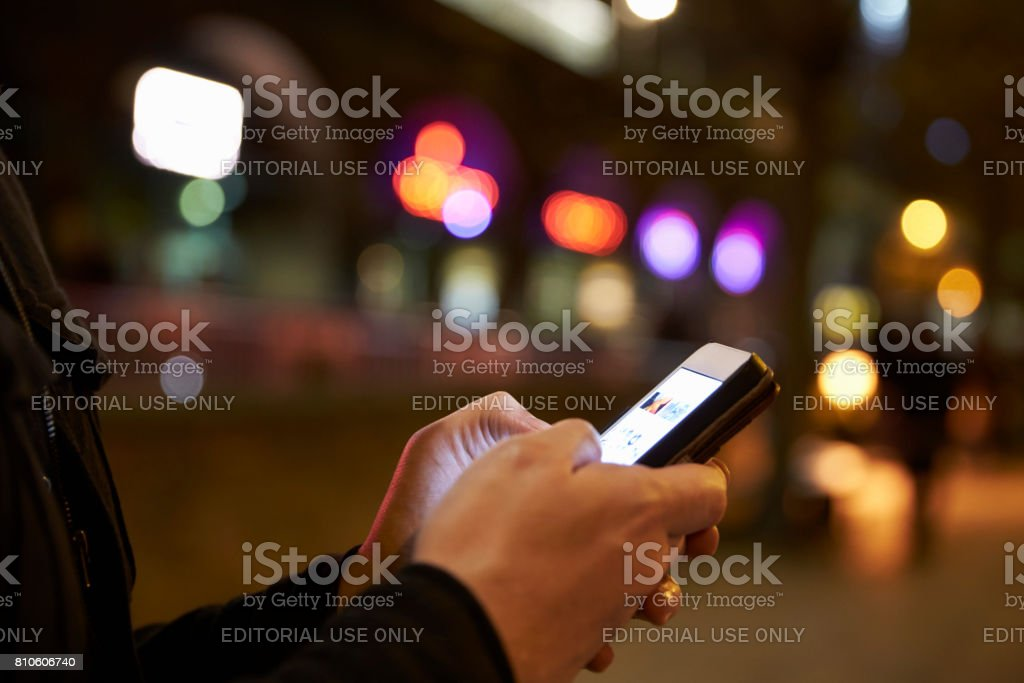 Manchester, UK - 4 May 2017: Person Using Mobile Phone Outside Apple Store In Birmingham stock photo