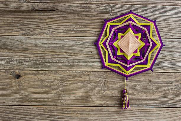 mandala, star of woolen threads, on wooden boards - buddhist tattoos stock-fotos und bilder