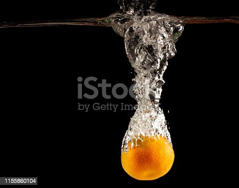 1169153675 istock photo Mandarin falls into water creating spray on a black background 1155860104