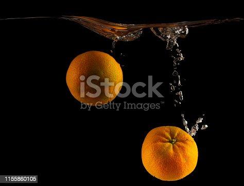 1169153675 istock photo Mandarin falls into water creating spray on a black background 1155860105