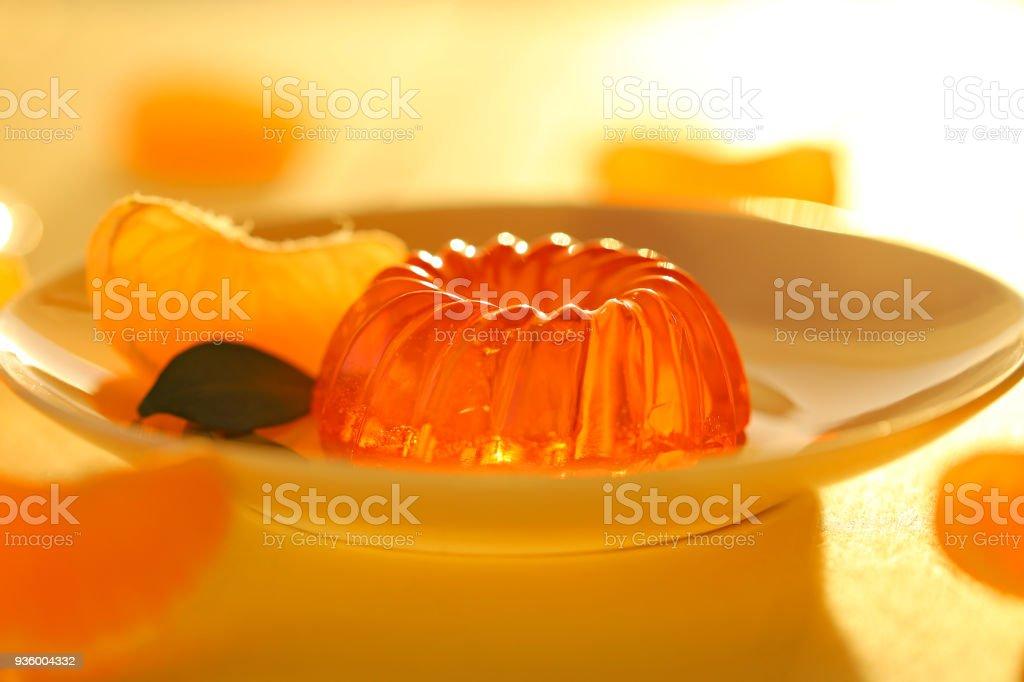 mandarin jelly. citrus jelly. orange jelly in dessert plate and slices of fresh, ripe tangerine on a wooden plank yellow background. Vegan dessert. Dietary sweetness stock photo