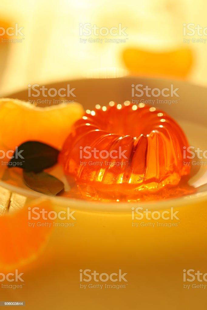 mandarin jelly. citrus jelly. orange jelly in white dessert plate and slices of fresh tangerine on a wooden plank yellow background. Vegan dessert. Dietary sweetness stock photo