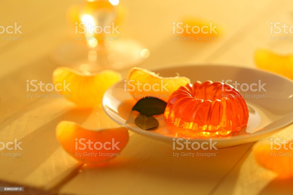 mandarin jelly. citrus jelly. orange jelly in white dessert plate and slices of fresh, ripe tangerine on a wooden yellow background. Vegan dessert. Dietary sweetness stock photo