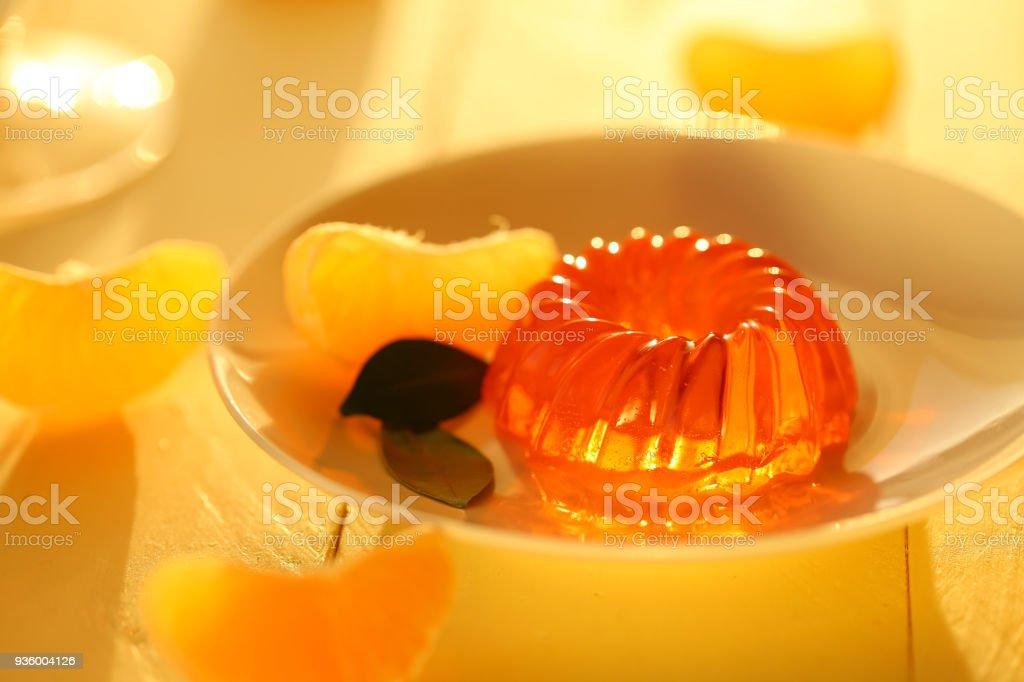 mandarin jelly. citrus jelly. orange jelly in white dessert plate and slices of ripe tangerine on a wooden plank yellow background. Vegan dessert. Dietary sweetness stock photo