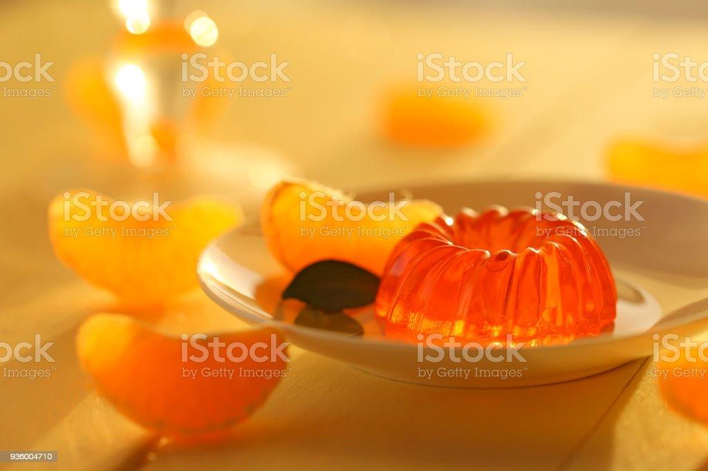 mandarin jelly. citrus jelly. orange jelly in white dessert plate and slices of fresh, ripe tangerine on a wooden plank yellow background. Vegan dessert. stock photo