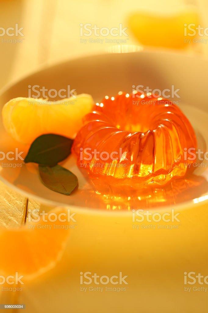 mandarin jelly. citrus jelly. orange jelly in white dessert plate and slices of fresh, ripe tangerine on a wooden plank yellow background. Vegan dessert. Dietary sweetness stock photo