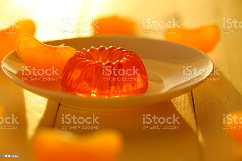 mandarin jelly. citrus jelly. orange jelly in white dessert plate and slices of fresh, ripe tangerine on a wooden plank yellow background. Dietary sweetness stock photo