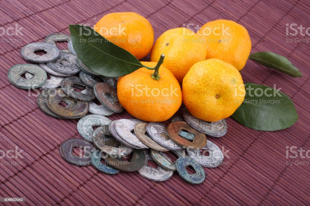 Mandarin Oranges And Ancient Chinese Coins On Bamboo Background