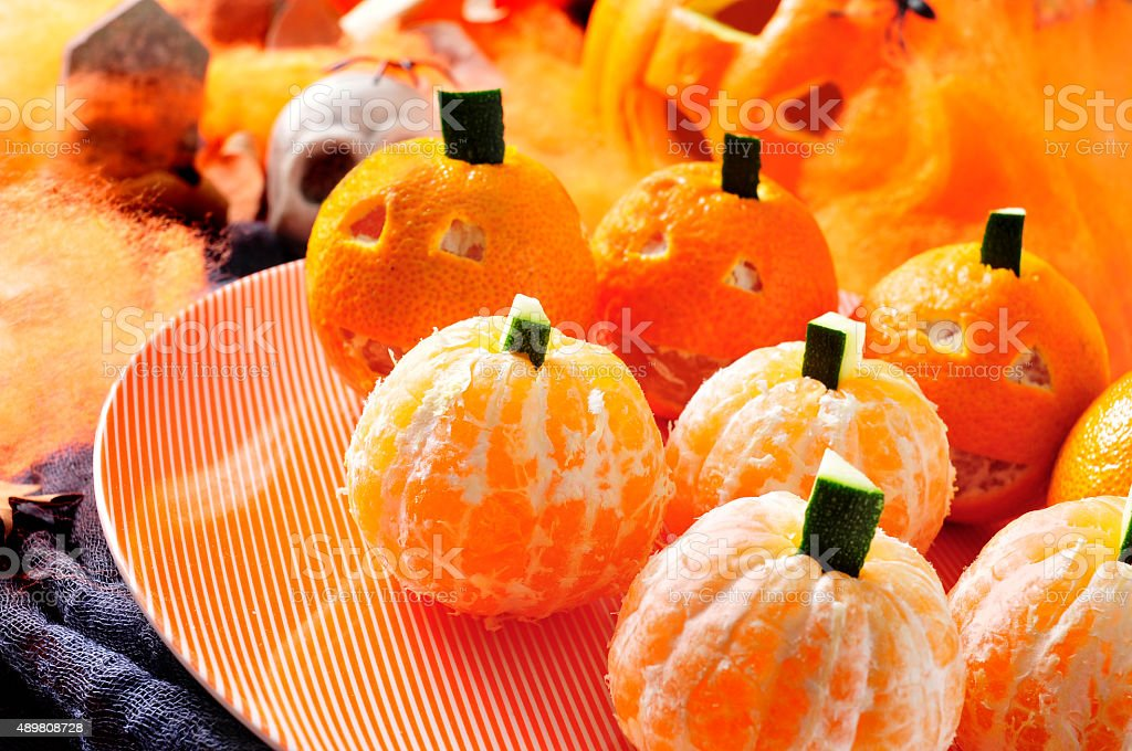 mandarines ornamented as Halloween pumpkins stock photo