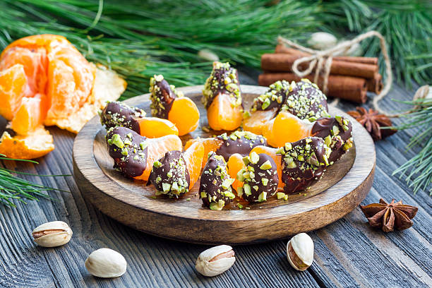 Mandarins covered with chocolate and pistachio on wooden plate stock photo