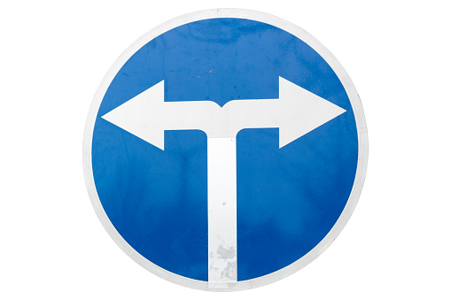 'Mandatory turn left and right ahead' round blue road sign isolated on white.