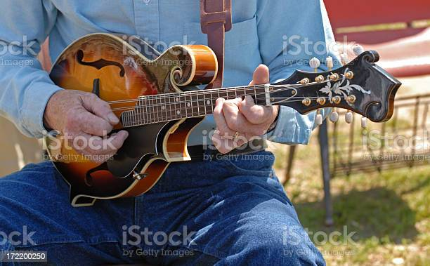 Old timer picks a bluegrass tune on a mandolin at a folk music festival. Need photos representing music