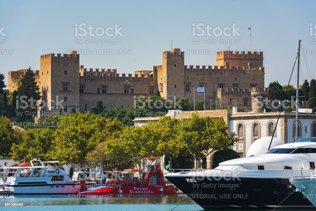 Mandraki Harbor with medieval fortress on a background in Rhodes Town, Rhodes island, Greece stock photo