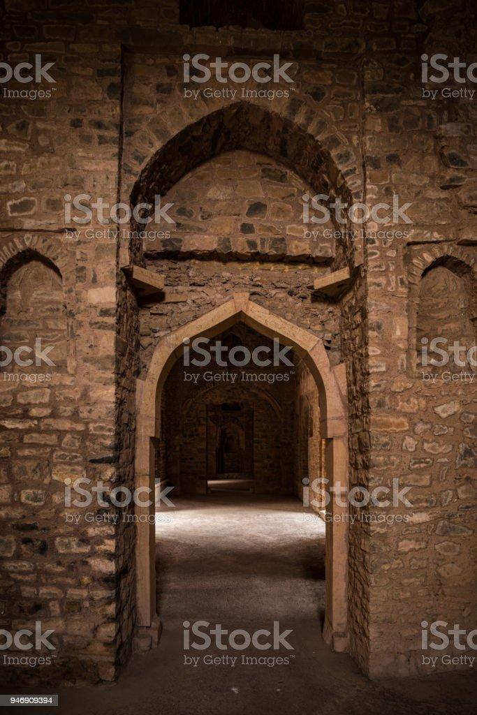 Mandu India, afghan ruins of islam kingdom, palace interior, mosque monument and muslim tomb. Sunshine from door in dark corridor. stock photo