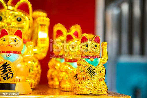 This is a horizontal, color photograph of lucky golden cats for sale in Hong Kong China.