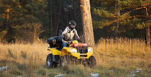 Maneuvering off-road ATV Horizontal action shot of a man in helmet and safety goggles riding quad bike with snowy autumn forest in the background. quadbike stock pictures, royalty-free photos & images