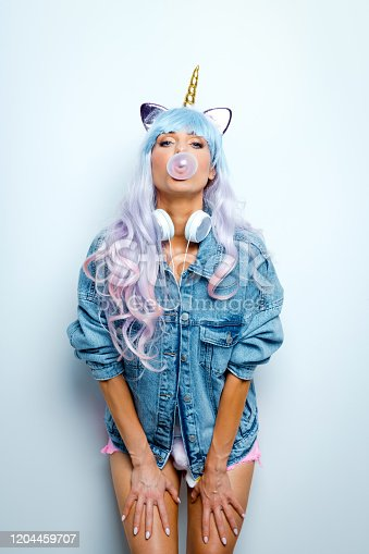 Portrait of beautiful blue and pink long hair young woman wearing oversized jeans jacket, unicorn horn headband and pink shorts. Cute girl chewing gum. Studio shot.
