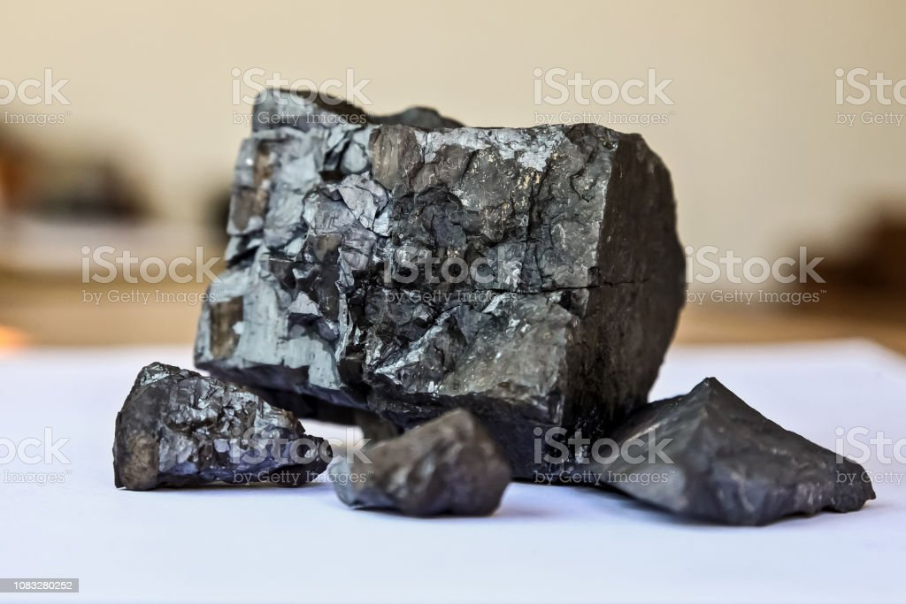 Close up of a selection of small Manganese Ore rocks on a white...