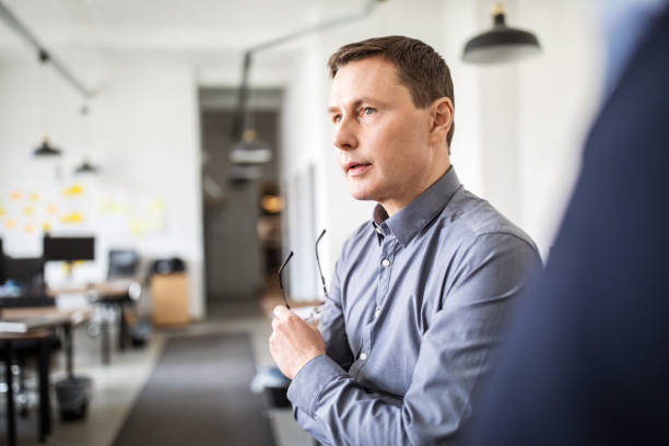 Manger discussing with colleagues in office stock photo