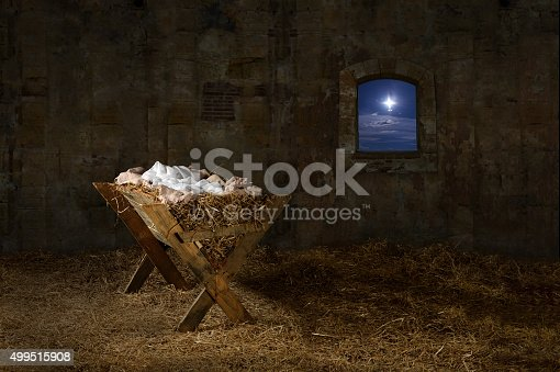 Manger in barn with window showing Christmas star