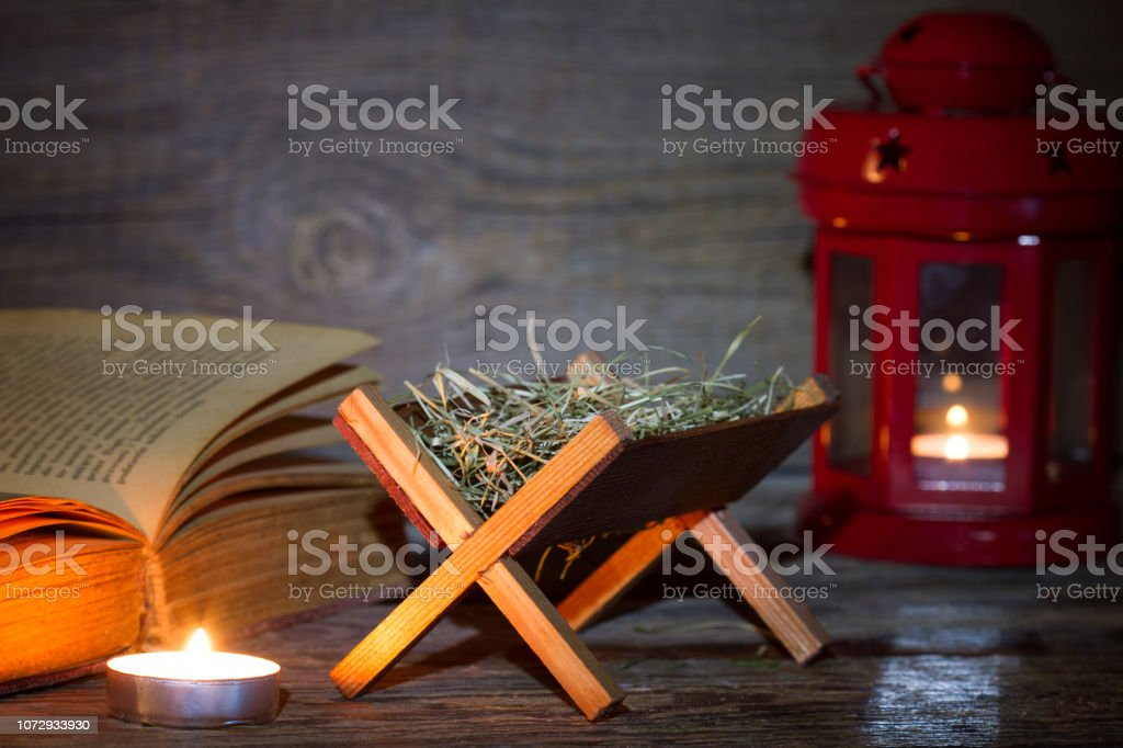 Manger nativity scene lantern and bible in night abstract christmas background stock photo