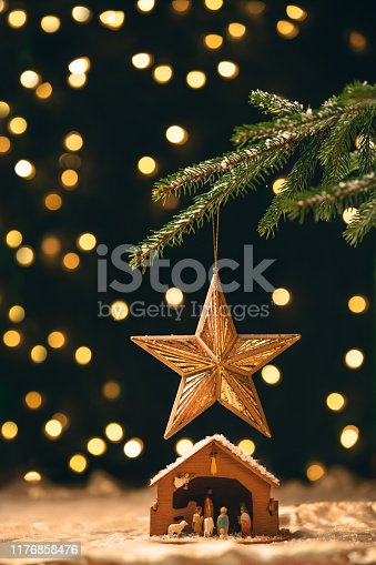 A manger sitting under a star ornament that is hanging from a Christmas tree with lights blurred behind.