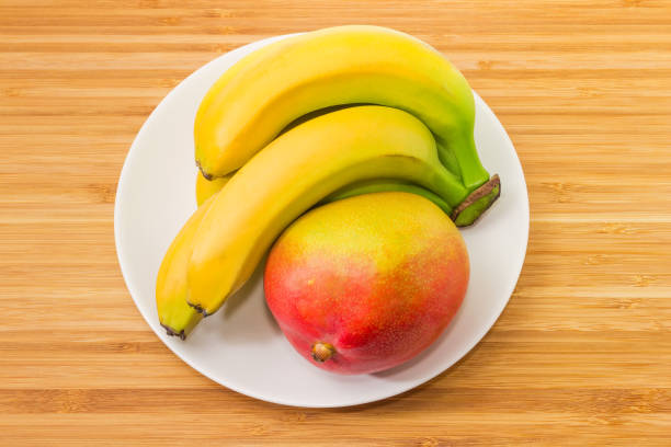 Mango and cluster of bananas on dish on wooden surface stock photo