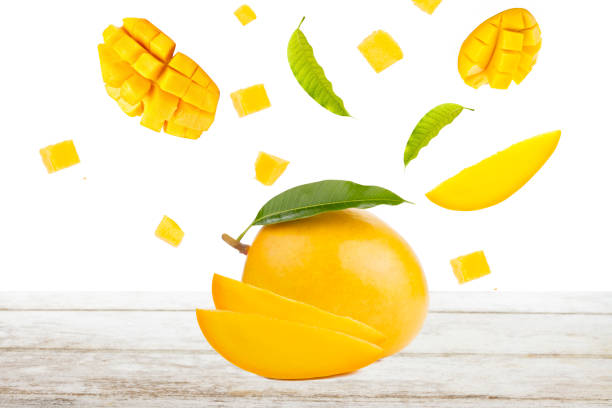 Mango and falling of cut slice with leaf on white wood Mango and falling of cut slice with leaf on white wood, isolated background mango stock pictures, royalty-free photos & images