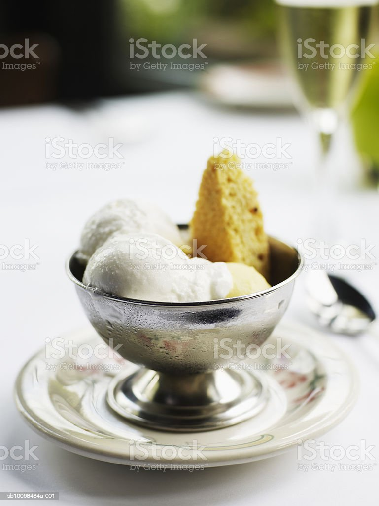 Mango and lemon gelato with cookie, glass of champagne in background foto de stock royalty-free