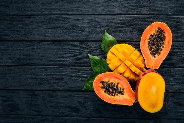 Mango and Papaya. Tropical Fruits. On a wooden background. Top view. Copy space. Mango and Papaya. Tropical Fruits. On a wooden background. Top view. Copy space. papaya smoothie stock pictures, royalty-free photos & images