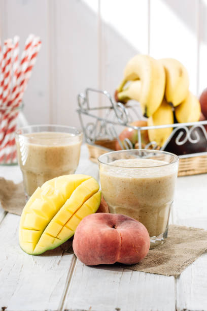 mango und pfirsich smoothie auf holztisch mit zutaten. - pfirsich milchshake stock-fotos und bilder