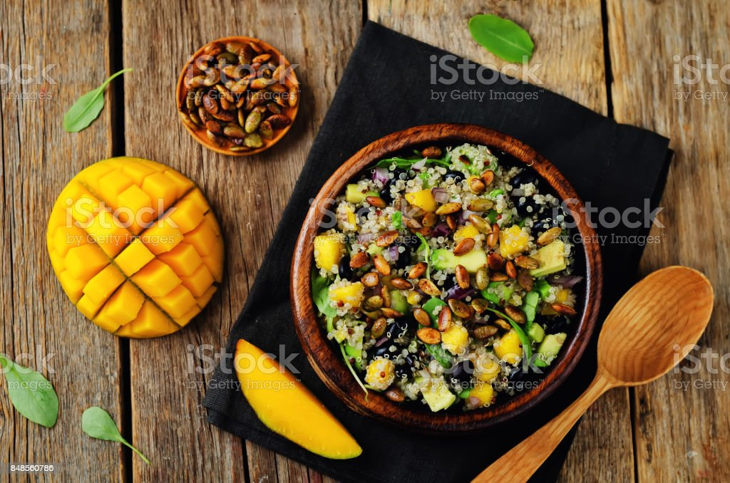 Mango black bean arugula pumpkin seed quinoa salad stock photo