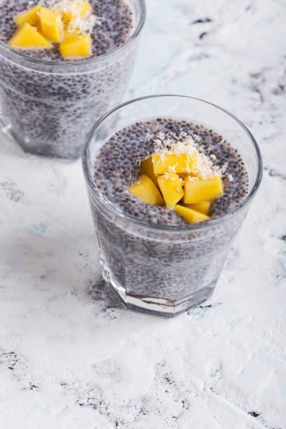 mango chia pudding mandel-milch in gläsern - chia pudding kokosmilch stock-fotos und bilder