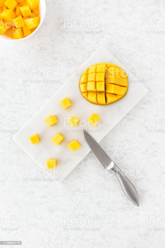 Mango Würfeln und geschnittene Mango halbe auf weißem Marmor – Foto