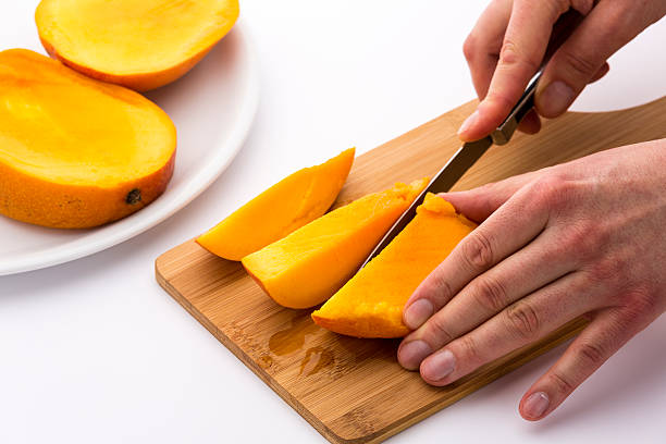 Mango Divided Into Thirds Being Subdivided Further stock photo