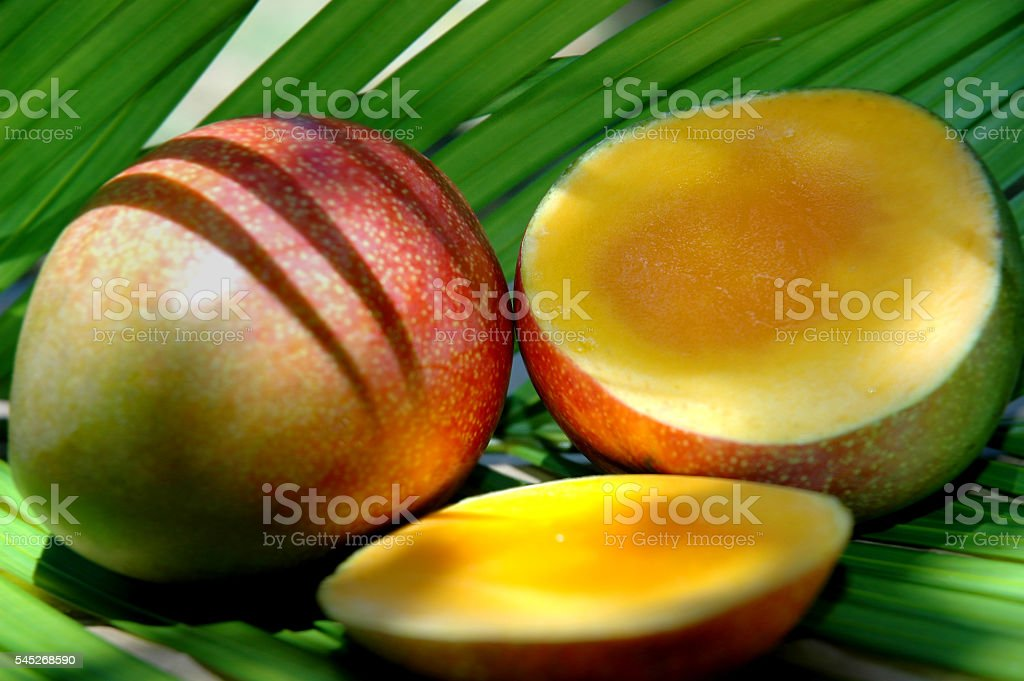 Mango fruit with slice and green leaves stock photo
