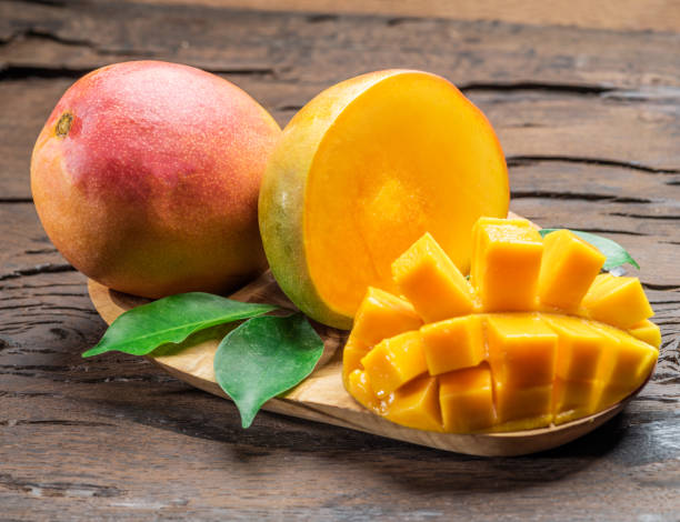 Mango fruits and mango slices. Mango fruits and mango slices on the old wooden table. mango stock pictures, royalty-free photos & images