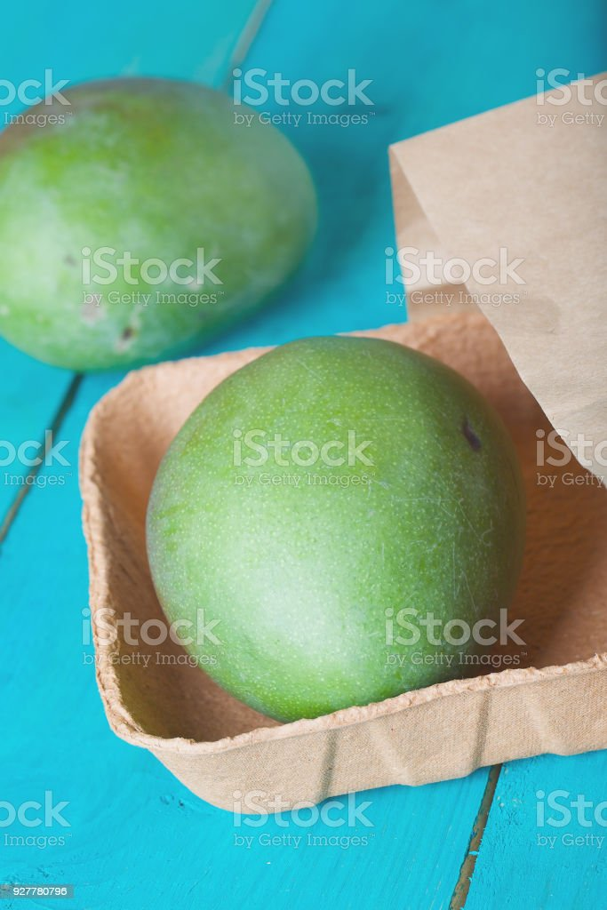 Mango in a paper bag on a wooden surface. stock photo