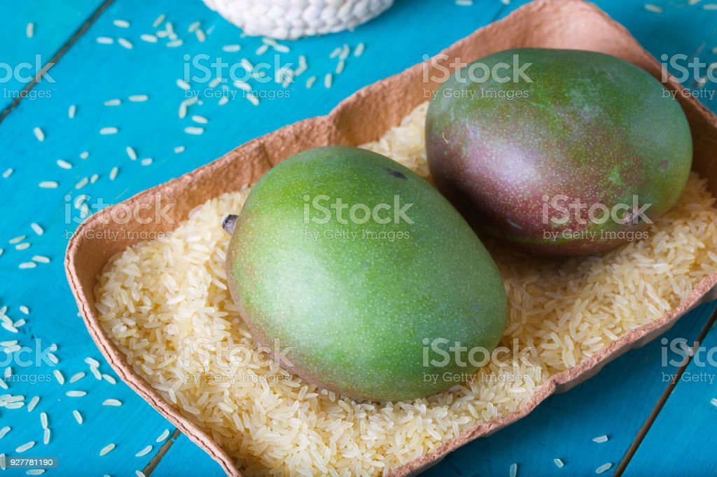 Mango in rice on a cyan wooden surface. stock photo