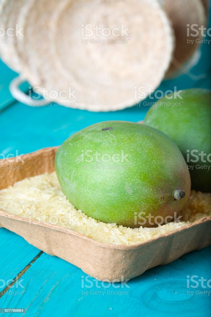 Mango in the paper plate full of parboiled rice for getting faster ripe. stock photo